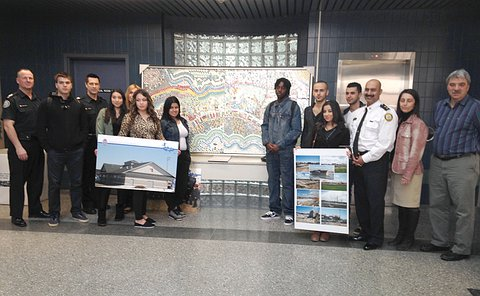 A group of teenage boys and girls with men and women in TPS uniform standing on either side of an art piece