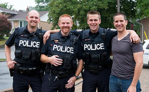 Three officers and man standing together smiling