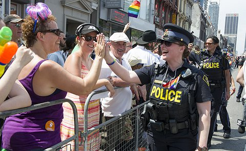 A woman in OPP uniform high-fives those lining a parade route