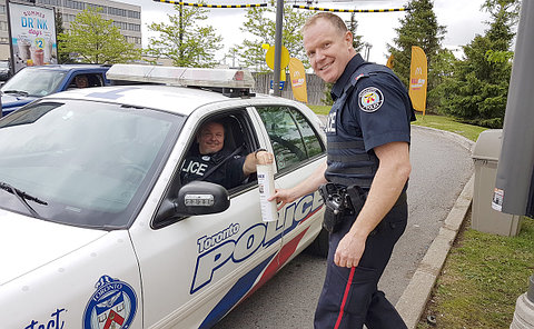 A man in a TPS scout car puts money in a cup held by another man in TPS uniform