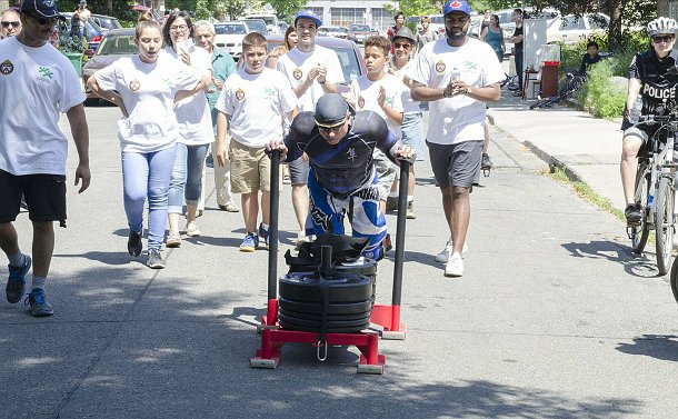 A group of people walk behind a man pushing a weighted sled