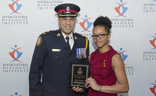 A man in Toronto Police uniform stands next to a woman holding a plaque