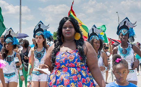 A woman in blue in the foreground, as several younger women march in costume behind her.