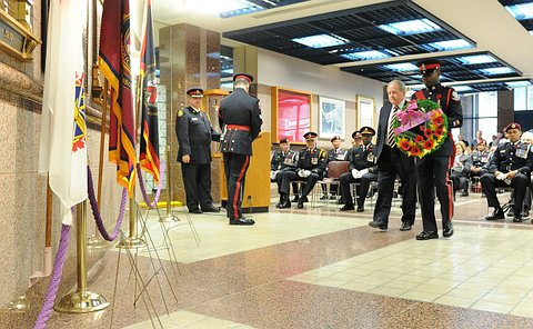 A man beside a man in TPS uniform holding a wreath