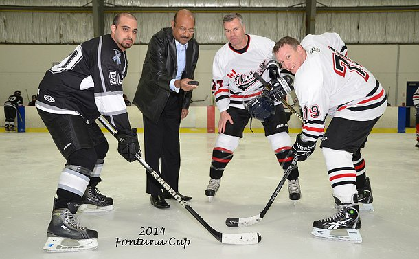 One man in TPS uniform holding a puck, three others in hockey gear and skates around a face off circle