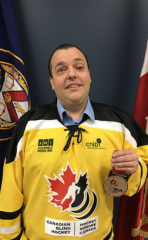 A man in a hockey jersey holding a medal