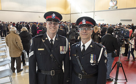 Two men in TPS uniform in a gym of people