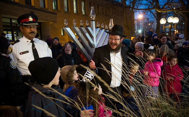 A man gestures near a large menorah surrounded by children