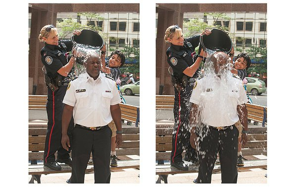 A woman in TPS uniform and a boy stand on a bench pouring a bucket of water on a man in TPS uniform