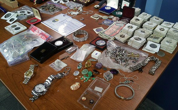 A display of old coins, bills and other jewellery recovered from the break-and-enters