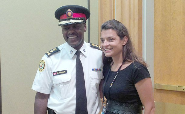 A man in TPS uniform stands beside a woman