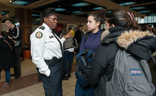 A woman in a white TPS uniform speaking to two students