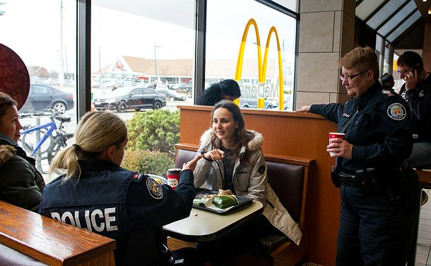 A woman in police uniform speaking to a woman sitting at a table while another woman in TPS uniform looks on