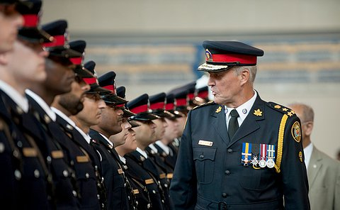 Chief Bill Blair stands in front of a line of officers looking at them.