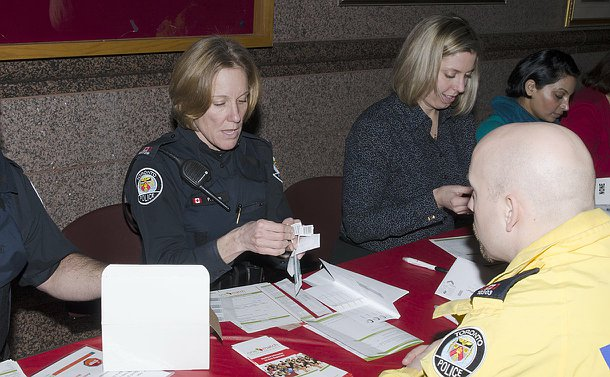 A woman in Toronto Police uniform holding a swab kit as another officer looks on