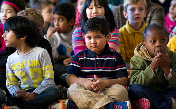 A young boy sitting crossed legged looking into the camera, there are children sitting beside him.