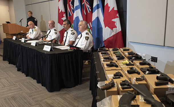 A group of people seated near a table of guns
