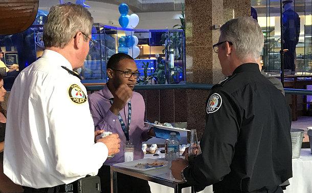 A man speaks to other men in TPS uniform