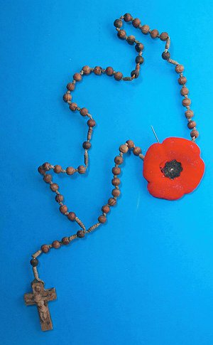 A necklace of beads with a crucifix and a red poppy attached