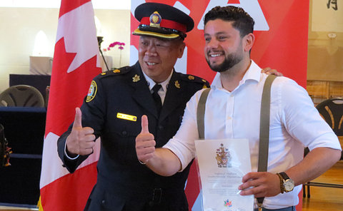 A man in TPS uniform beside another man giving thumbs up