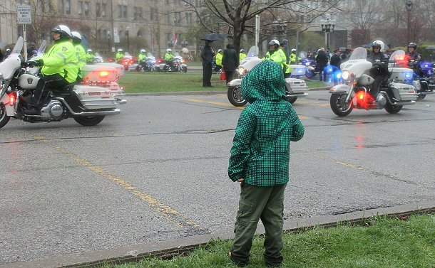 A boy facing back, standing on the curb looking at the passing motorcycles