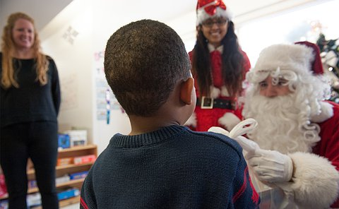 A Santa hands over a bag to a child while two women look on smiling