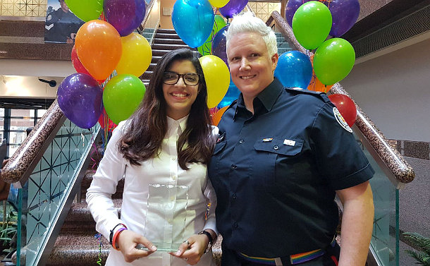 A woman in TPS uniform with a woman holding a glass award