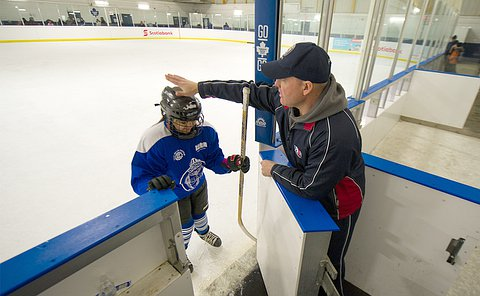 A man pats a child in hockey uniform on the helmet as she enters the bench