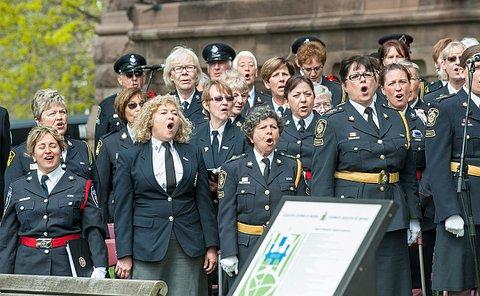 women in uniform singing in a choir.
