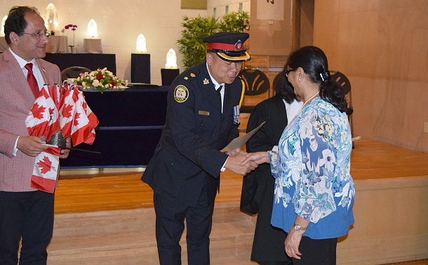 A man in TPS uniform shakes hands with a woman