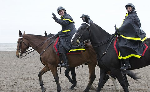 A man in TPS uniform on horseback waves