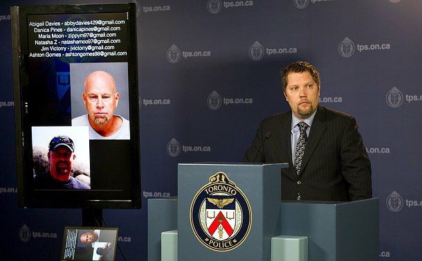A Toronto Police detective stands behind a podium in a suit with a tv screen to his right which shows two photos of the same man.