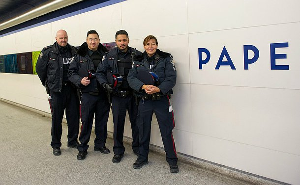 Three men and one woman in TPS uniform lined up against a wall with the word Pape