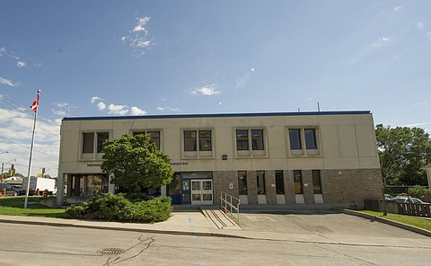 """A building with """"No. 13 Division"""" sign and a Canadian flag flying beside it"""