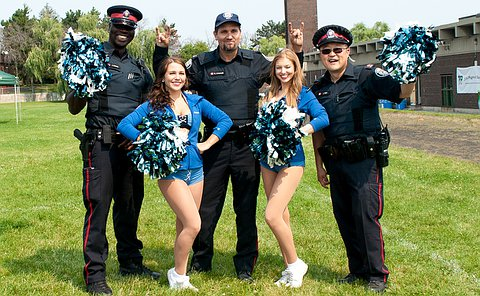three uniformed officers smile and pose with two cheerleaders in Toronto Argonauts uniforms.