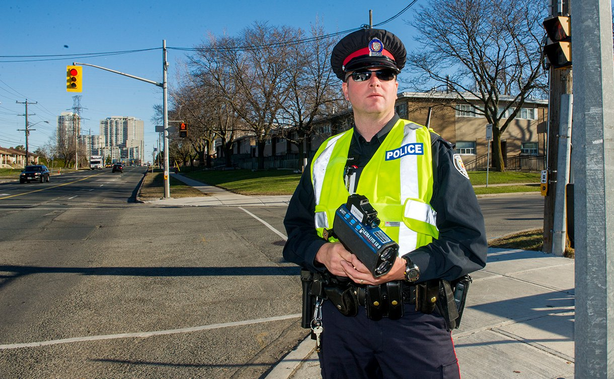 A male officer in uniform standing at an intersection.