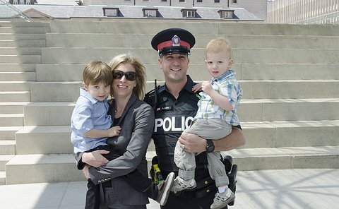 A woman and man in TPS uniform holding two boys