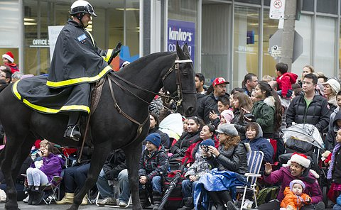An officer on horseback waves to a crowd lining the street. A woman and child wave back.