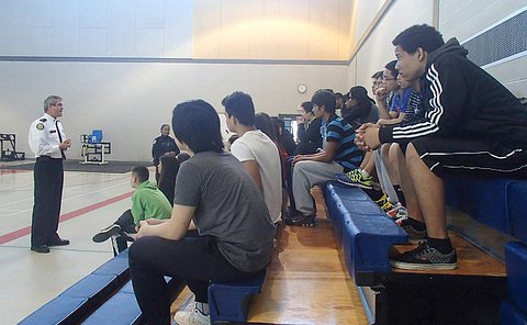 A man in TPS uniform in front of a group of teens on bleachers in a gym