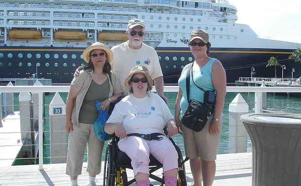 Three women and one man in centre on deck of a boat with a cruise ship behind them. One woman seated in a wheelchair