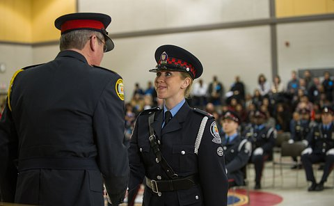 A woman in uniform shaking hands with the chief.