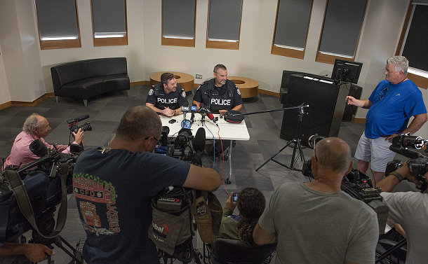 Two men in TPS uniform seated at a table with microphones and cameras pointed at them