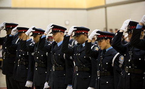 officers in auxiliary uniforms with their hats in their hands.