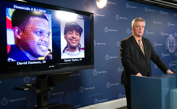 A man in a suit standing at a podium, next to him is a tv screen with images of the two victims of the shooting