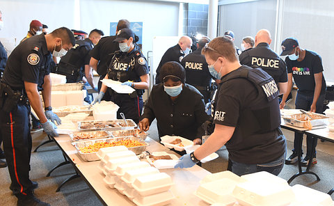 A group of people and police at tables full of food