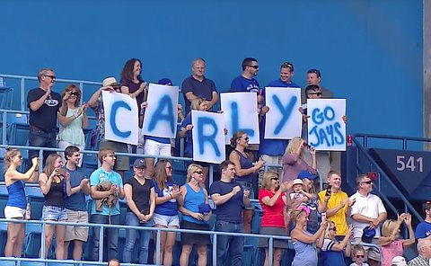 A group of people in stadium seating holding signs spelling out C-A-R-L-Y and Go Jays