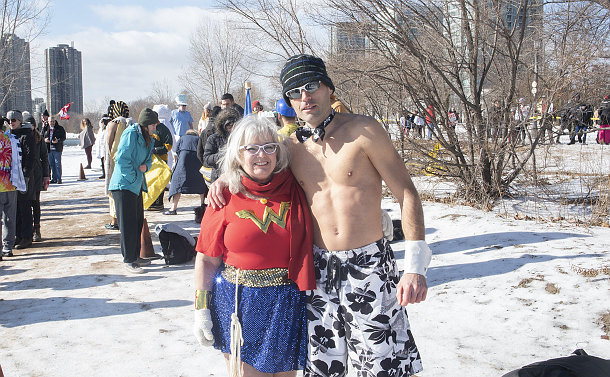 A woman in a superhero uniform and a man in shorts stand on a frozen beach