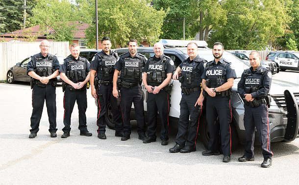 A group of police officers standing in front of a police vehicle in a parking lot