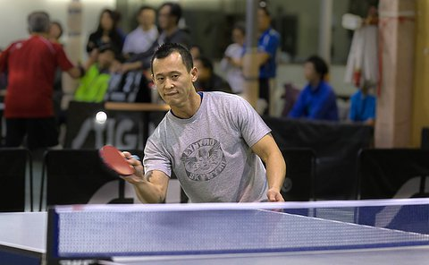 A man hits a ball with a table tennis racket at the end of the table