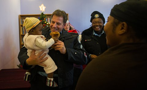 an officer in auxiliary uniform holding a baby and laughing as she plays with a stuffed toy